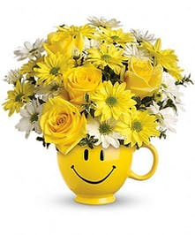 Mug filled with fresh cut yellow flowers